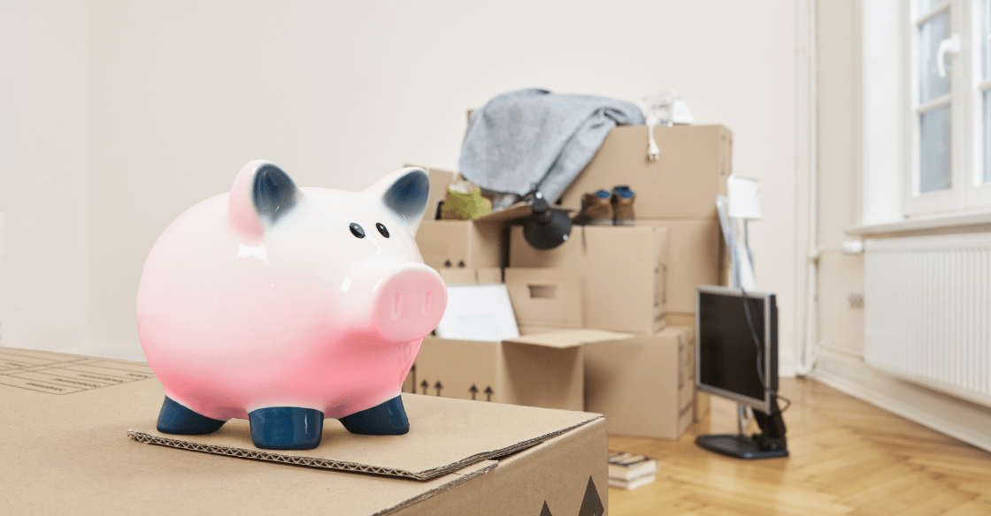 Piggy bank on a moving box showing the cost of storage units with several packed belongings in the background.