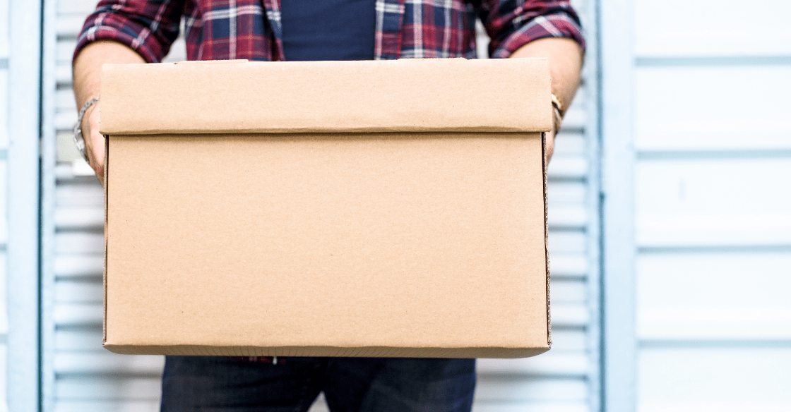 Man holding a moving cardboard box in front of a storage door