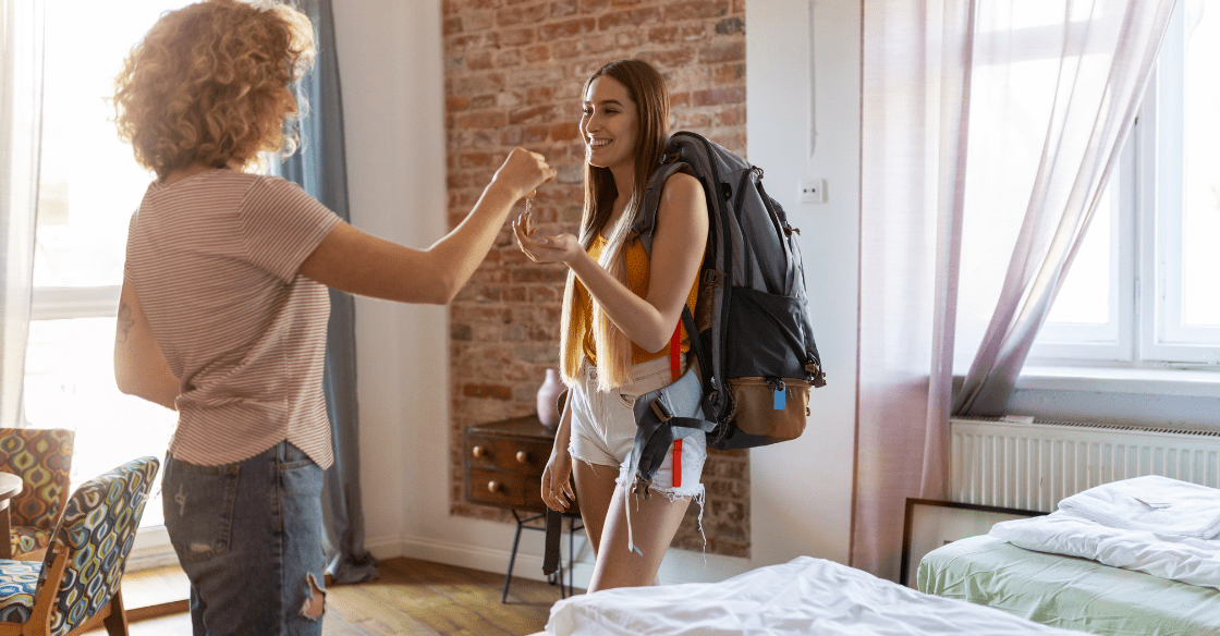 A homeowner passes keys to a guest after preparing her home for Airbnb.